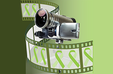 A digital camera on a green background & film reel. On the film reel there are green ribbons.