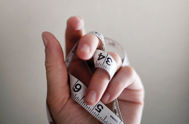 Stock photo of hand wrapped with a measuring tape