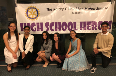 Student honorees in front of a High School Heroes Banner