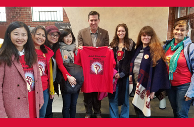 Line up of students with Asm Kevin Mullin holding red Adult Ed Matters t-shirt