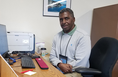 Demetrius Booker at his desk with computer