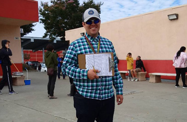 Smiling Edgar in Cap and Blue Checked Shirt, Holding Clipboard, in the Quad