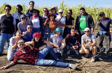 Happy students in an Agricultural setting - the student in front is lying on his die facing the cam