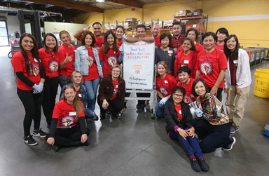 Group of people dressed in red with sign noting how much work they did at Second Harvest Food Bank