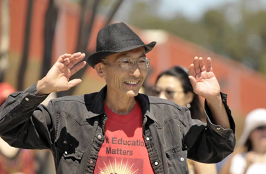 Smiling man in black fedora and black shirt, arms raised