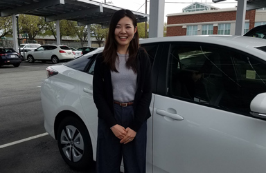 Woman smiling in front of parked car - under solar panels at SMAS