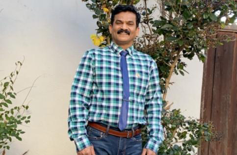Smiling man with mustache blue checked shirt and blue tie