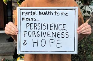 Cropped photo with just a person's hands holding a sign that reads: Mental Health to me means Persistence, Forgiveness, Hope
