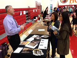 Students talking to college rep at College Fair