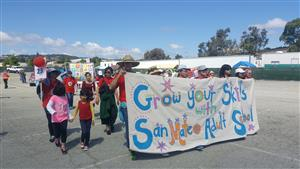Students march in parade with banner:  Grow Your Skills with SMAS
