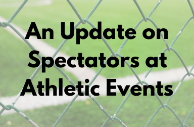 Looking through a chain link fence at a football field with text that reads: Update on Spectators