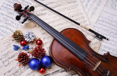 iStock_violin on stack of music sheets with decorations mixed in