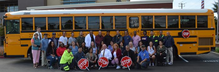 Transportation Department staff in front of a school bus